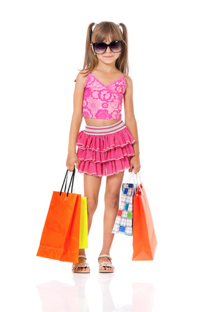 Beautiful little girl with shopping bags, isolated on white background photo