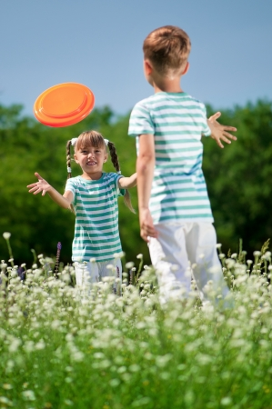 Happy boy and little girl playing frisbee on a meadow in a sunny day