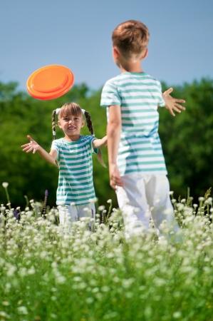 Ragazzo felice e bambina giocare a frisbee su un prato in una giornata di sole