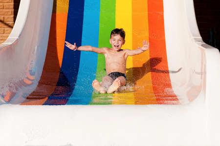 Boy has into pool after going down water slide during summer Standard-Bild