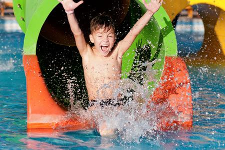 Boy tiene en la piscina después de ir abajo tobogán de agua durante el verano Foto de archivo