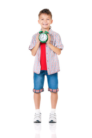 Happy teen boy with alarm clock, isolated on white background photo