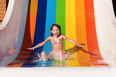 Little girl has into pool after going down water slide during summer