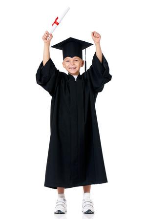 birrete de graduacion: Graduado feliz estudiante de niño en el manto con el diploma, aislado en fondo blanco Foto de archivo