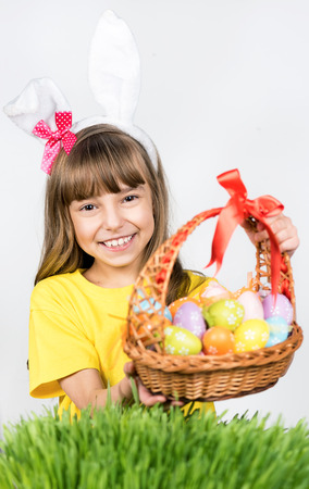 Beautiful little girl dressed in bunny ears is holding  basket with Easter eggs on a gray background photo
