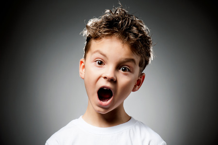 making face: Portrait of boy surprised on gray background Stock Photo