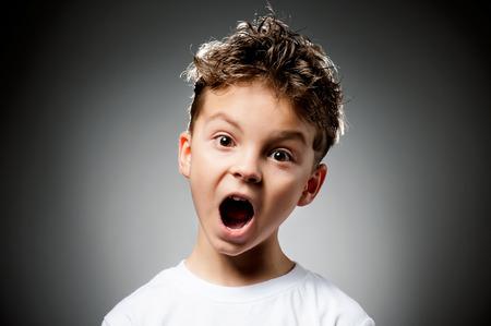 Portrait of boy surprised on gray background Foto de archivo