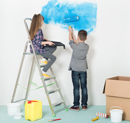 family activities: Happy children -  brother and sister, makes repairs at home. Boy and girl painting wall at home.