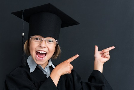 white back: Cute pupil in mortar board pointing at something at the black chalkboard in classroom. Stock Photo
