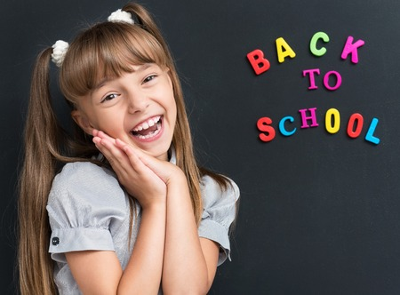 happily: Photo of adorable young cheering girl looking at camera at the black chalkboard in classroom.