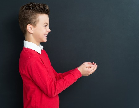 11 years: Portrait of adorable young boy 11 years old posing at the black chalkboard in classroom. Stock Photo