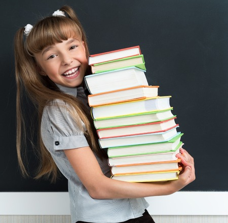 Back to school concept. Happy schoolgirl with books at the black chalkboard in classroom.