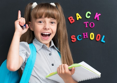 personas de espalda: Volver al concepto de escuela. Colegiala feliz con la mochila y cuaderno en el pizarrón negro en el aula.