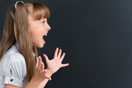 Portrait of schoolgirl crying at the black chalkboard in classroom.