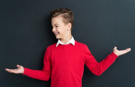 Portrait of adorable young boy 11 years old posing at the black chalkboard in classroom. Stock Photo - 41654168