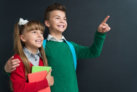 little: Happy little girl and boy pointing at something at the black chalkboard in classroom.