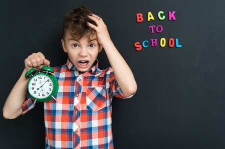 wonder: Back to school concept. Boy with big green alarm clock at the black chalkboard in classroom.