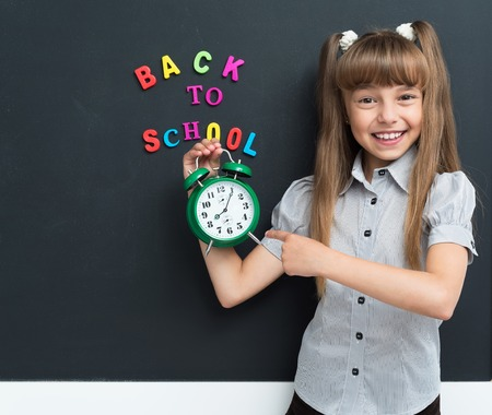 Back to school concept. Happy girl with big green alarm clock at the black chalkboard in classroom. Stock Photo