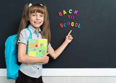 young schoolgirl: Back to school concept. Cheerful schoolgirl with backpack at the black chalkboard in classroom.