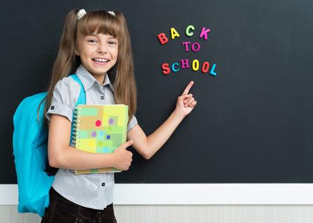 backpack: Volver al concepto de escuela. Colegiala alegre con la mochila en el pizarrón negro en el aula.