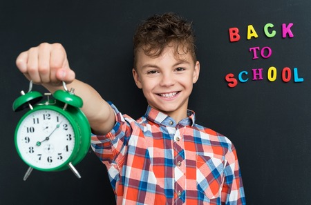 Back to school concept. Boy with big green alarm clock on black chalkboard background. Stock Photo