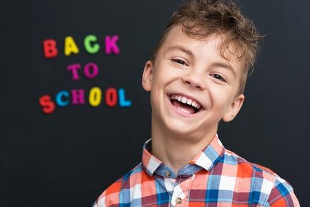 niños riendose: Volver al concepto de escuela. Colegial alegre en el pizarrón negro en el aula.