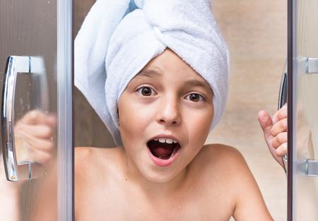 mojada: Retrato de niña con la toalla en la cabeza. La muchacha toma una ducha en el baño. Foto de archivo
