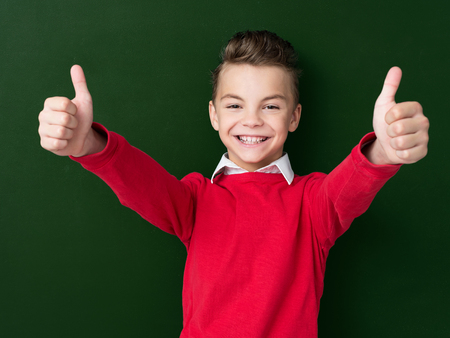 standing up: Portrait of adorable young boy showing thumbs up sign using both hands at the dark green chalkboard in classroom.