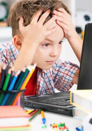 comprehension: Portrait of despairing adolescent boy working on computer at the table