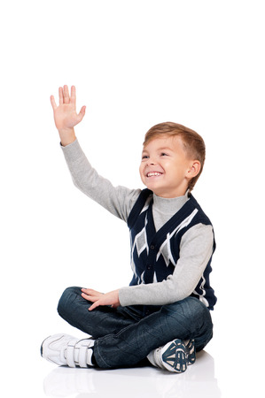 sitting up: Smiling boy sitting on floor and looks into the distance isolated on white background