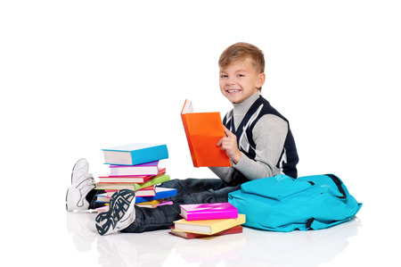 8   9 years: Happy schoolboy sitting on floor with backpack and books isolated on white background