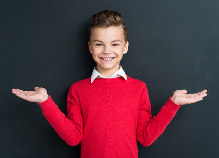 bad boy: Portrait of adorable young boy 11 years old posing at the black chalkboard in classroom. Stock Photo