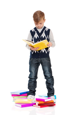 Full length portrait of a happy schoolboy with books isolated on white background