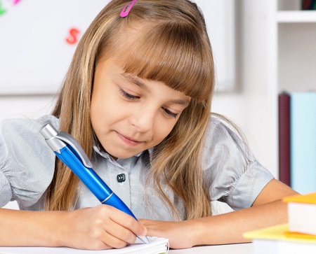 private schools: Little girl sitting at desk in the classroom, doing homework at the table.