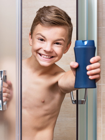 Smiling beautiful teen boy takes a shower in the bathroom