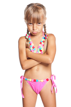 Unhappy little girl in swimsuit isolated on white background