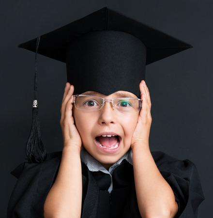 graduate hat: Portrait of shocked little girl wearing black graduation gown at the black chalkboard in classroom