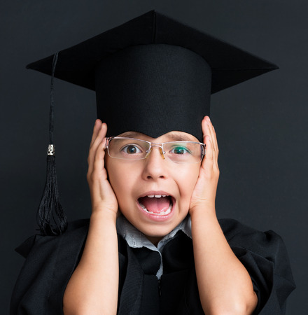 graduado: Retrato de la niña sorprendida que desgasta el vestido negro de la graduación en la pizarra negro en el aula Foto de archivo