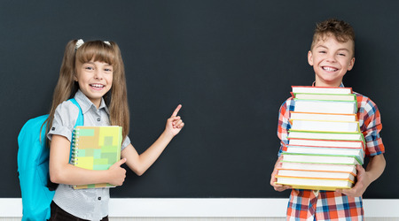 indicating: Back to school concept. Happy little girl and boy with books at the black chalkboard in classroom. Stock Photo