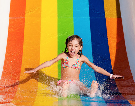 flowing water: Little girl has into pool after going down water slide during summer
