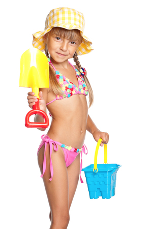 swim: Adorable little girl standing in swimming wear and panama hat with bucket and spade, isolated on white background