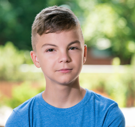 Portrait of a teen boy 12-14 year old, posing outdoors. Stock Photo