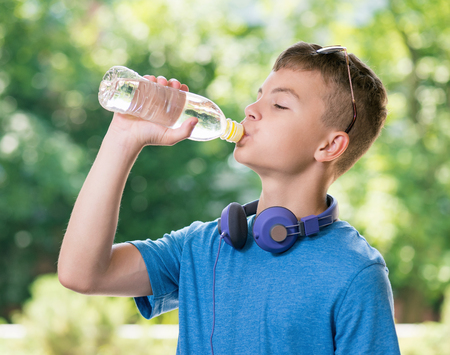 Teen boy 12-14 year old drinking fresh water from a bottle. Student teenager with headphones and sunglasses posing outdoors. Stock Photo