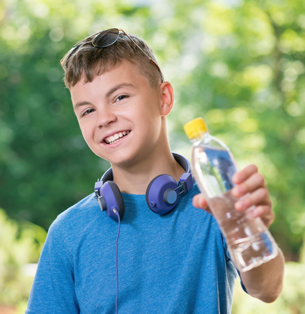 cool man: Teen boy 12-14 year old with bottle of fresh water. Student teenager with headphones and sunglasses posing outdoors.