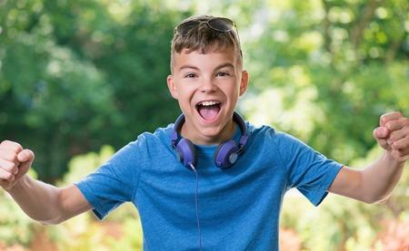 Victoire hurlant adolescent garçon 12-14 ans. Vainqueur garçon avec un casque et des lunettes de soleil posant à l'extérieur.