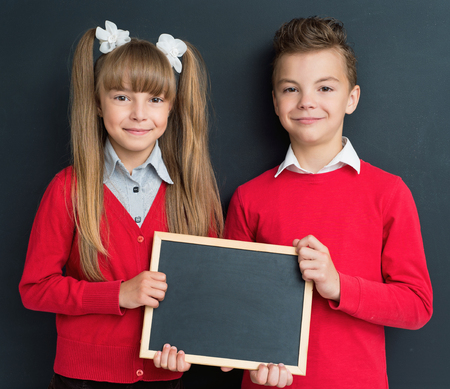 school boy: Happy pupil - teen boy and girl with small blackboard in front of a big chalkboard. Back to school concept. Stock Photo