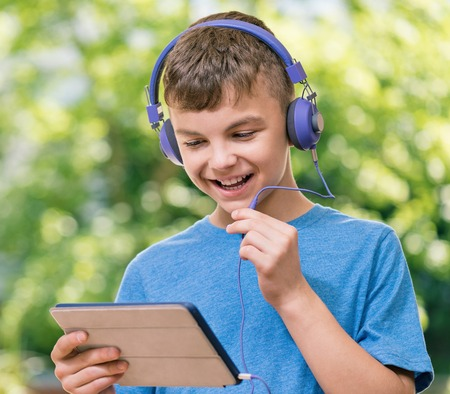 computer education: Outdoor portrait of happy teen boy 12-14 year old chating with family or friends using tablet Stock Photo