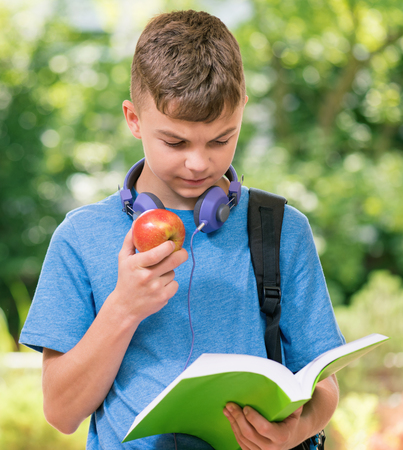 Outdoor portrait of happy teen boy 12-14 year old with books and apple. Back to school concept.