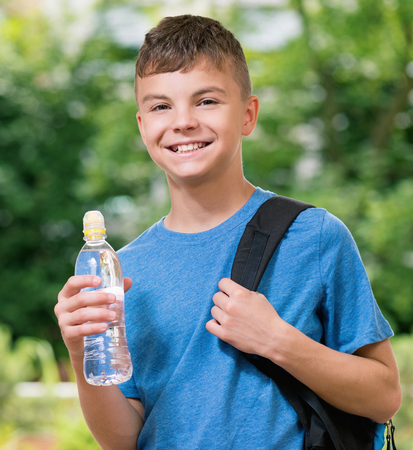 water bottle: Teen boy 12-14 year old with schoolbag and bottle of fresh. Student teenager posing outdoors.
