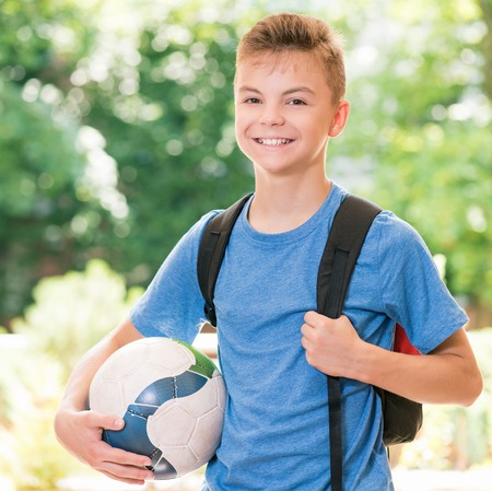 Outdoor portrait of happy teen boy 12-14 year old with soccer ball and backpack. Back to school concept.